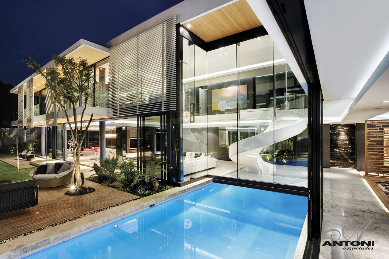 Swimming pool and glass wall as part of facade at night