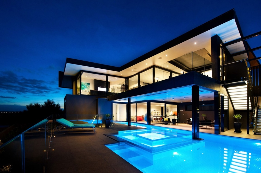 black home with blue lit swimming pool - Blue House Design