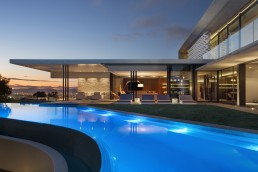 Outdoor swimming pool in concrete and glass modern home
