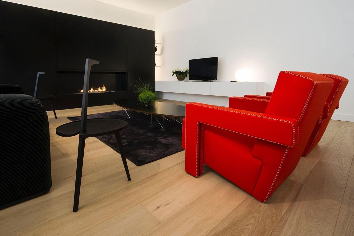Red chair and black furniture in minimalist apartment by Filip Deslee