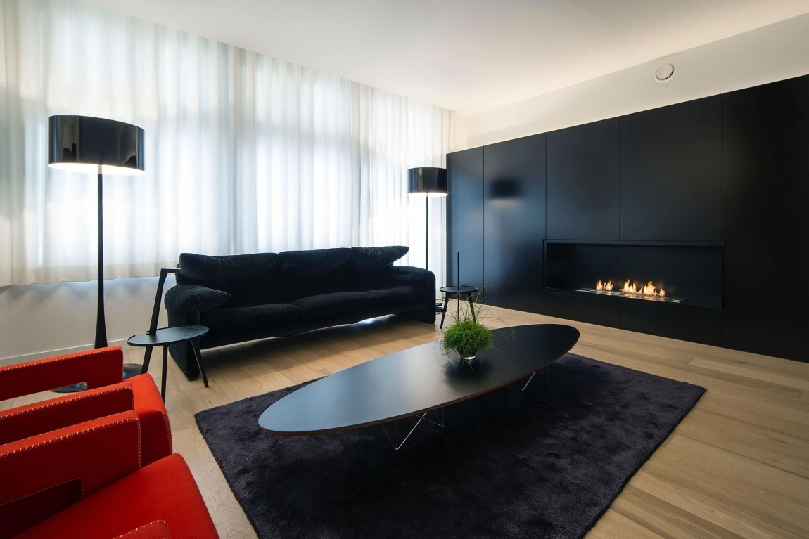 Black rug and coffee table in minimalist apartment by Filip Deslee