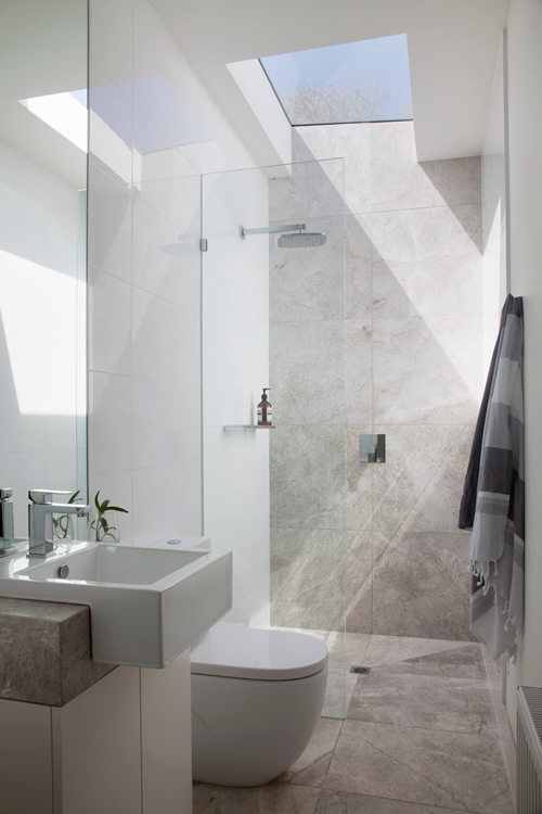 walk in shower in small bathroom with skylight