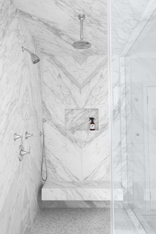 walk in shower with a seat and marble