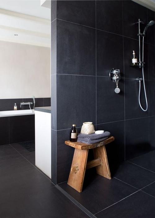 dark open walk in shower with a seat