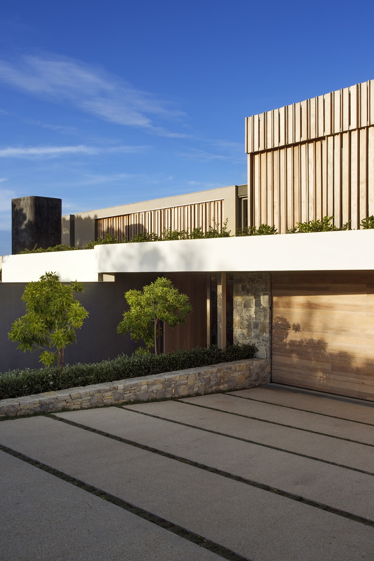 Entrance to the modern home with modern home with wooden facade by SAOTA