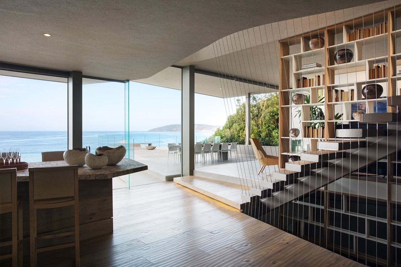 Glass walls in modern home with wooden facade by SAOTA