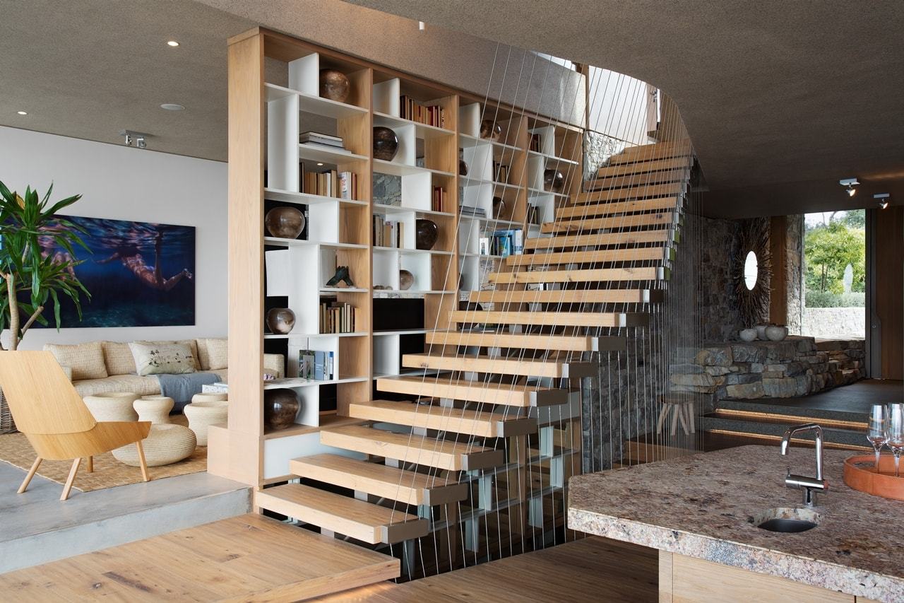 Wooden stairs in modern home with wooden facade by SAOTA