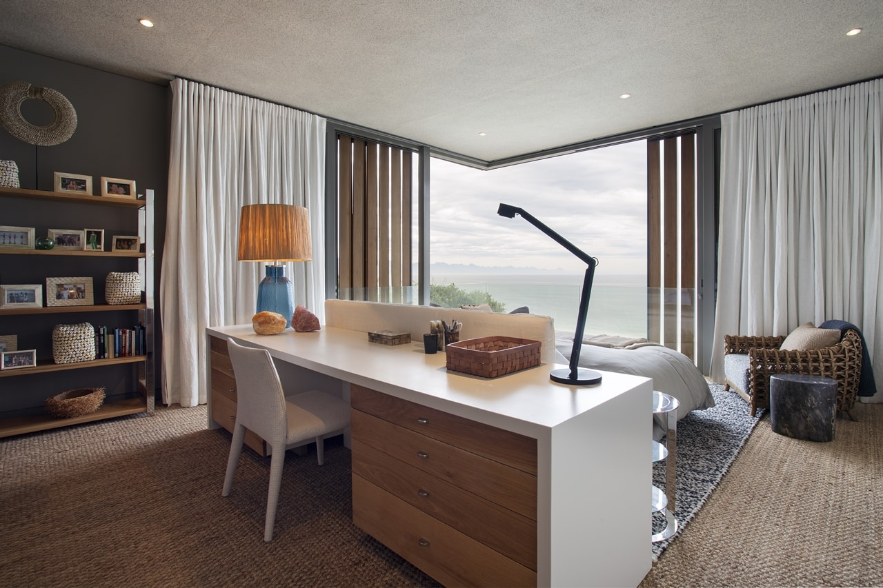 Bedroom desk in modern home with wooden facade by SAOTA