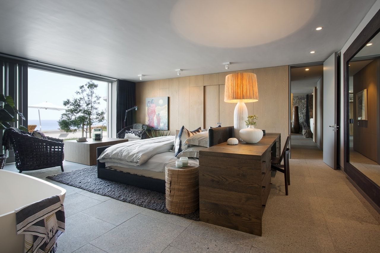 Large bedroom in modern home with wooden facade by SAOTA