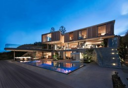 Modern home with wooden facade by SAOTA at night