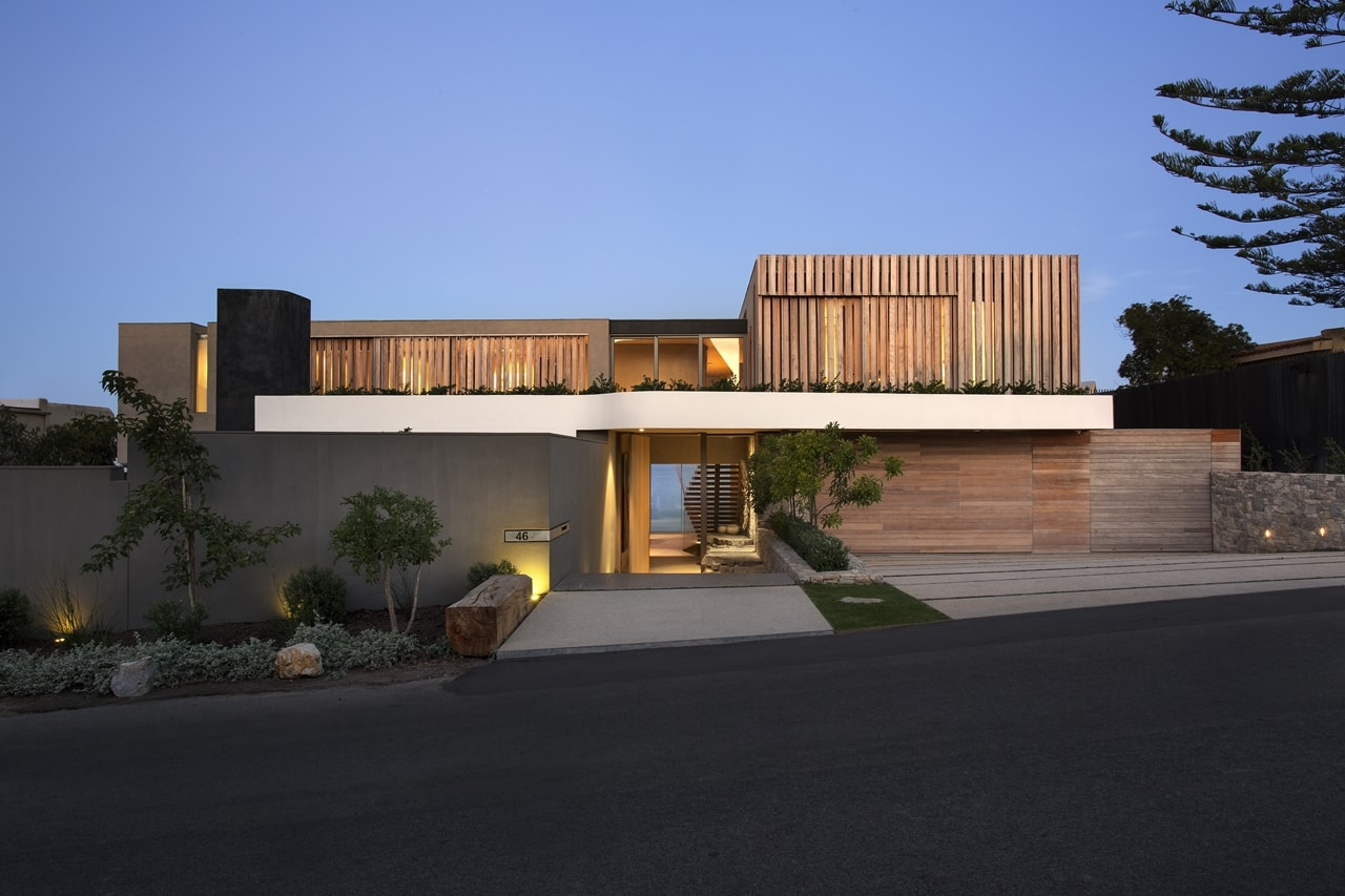 Front view of modern home with wooden facade by SAOTA at night