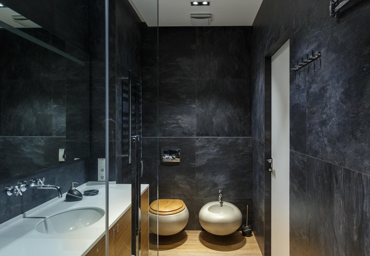 Dark bathroom in modern apartment by SVOYA
