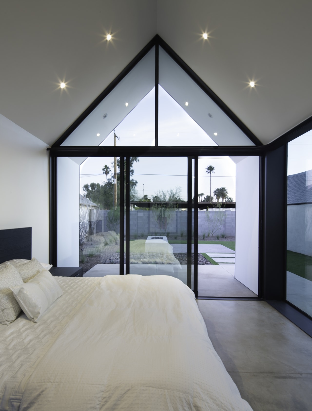 Modern bedroom with glass wall renovated by Chen + Suchart Studio