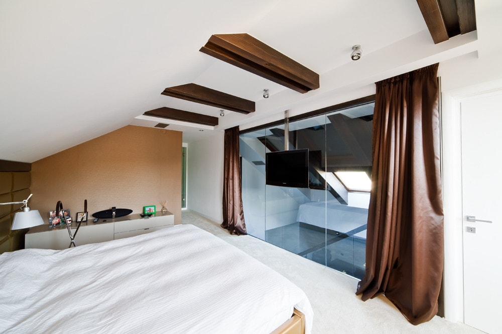 Modern attic bedroom with glass wall