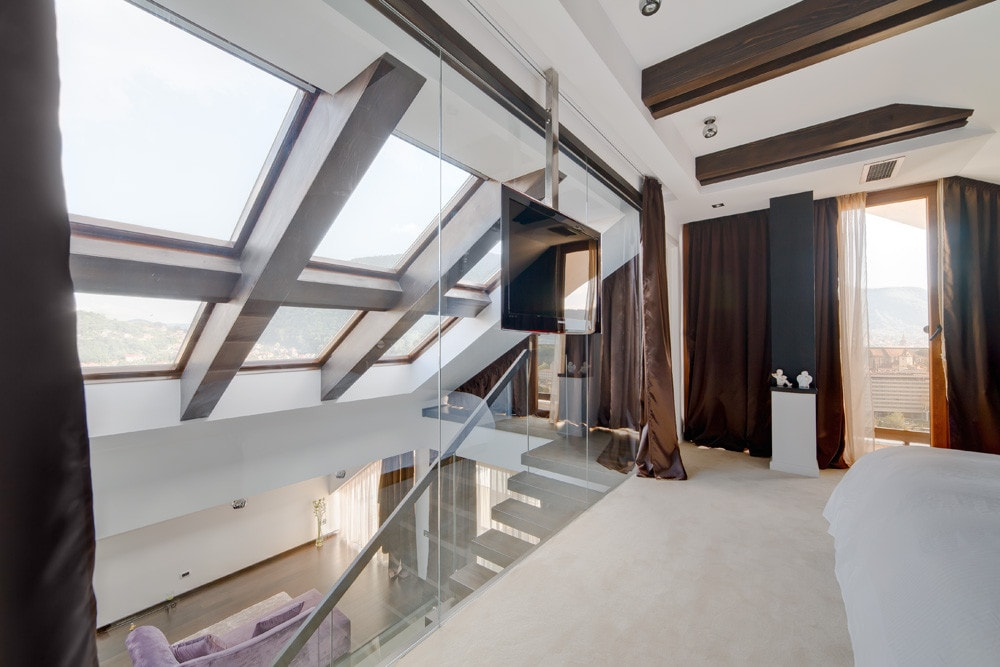 Roof windows and glass wall in modern bedroom