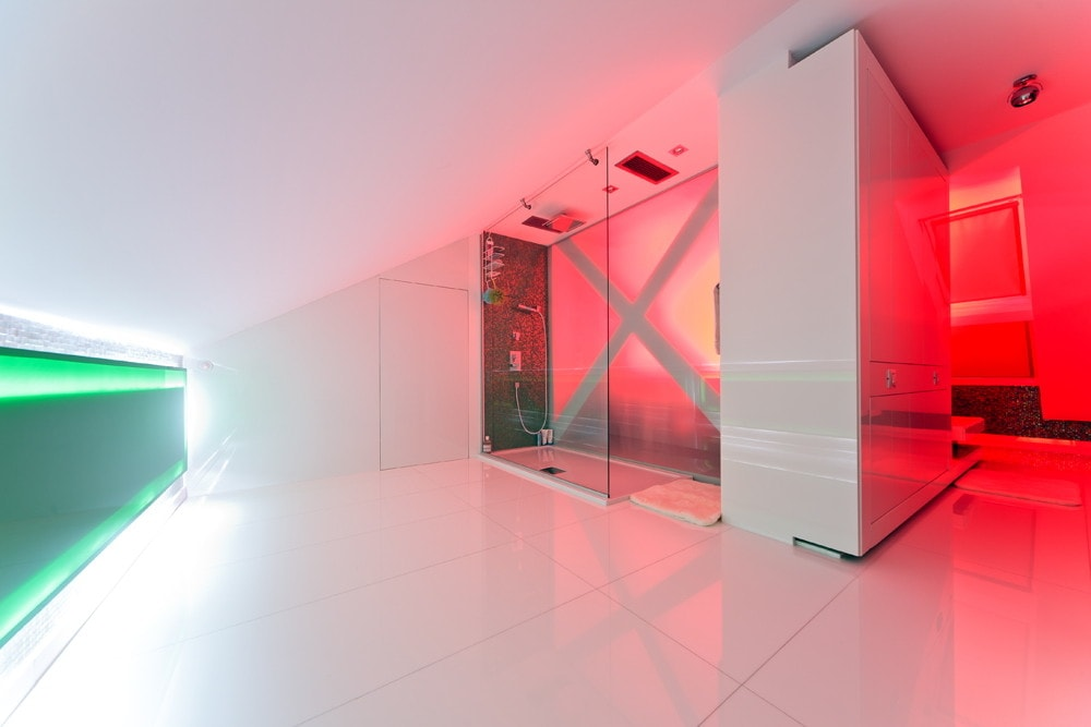Modern bathroom with red lighting in triplex apartment with glass floor