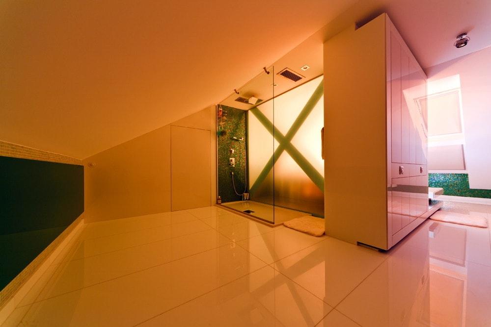 Modern bathroom and orange lighting in triplex apartment with glass floor