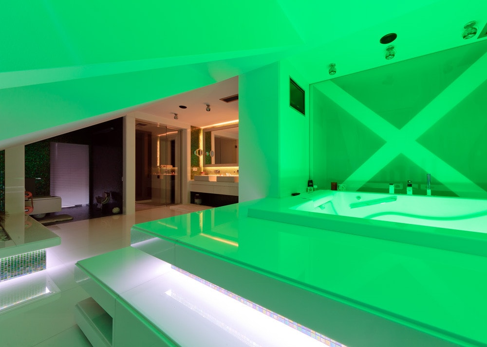 Modern bathroom with green lighting in triplex apartment with glass floor