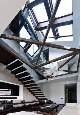 Glass floor design and living room with staircase in modern triplex apartment