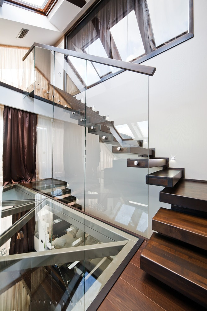 Wooden staircase and glass floor design in modern triplex apartment