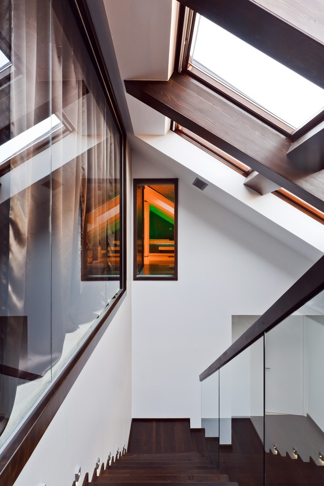 Glass walls and staircase in modern triplex apartment