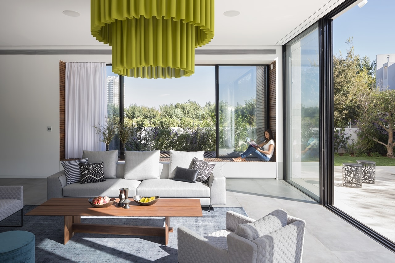 Living room with sliding glass doors in simple modern home by Sachar-Rozenfeld Architects